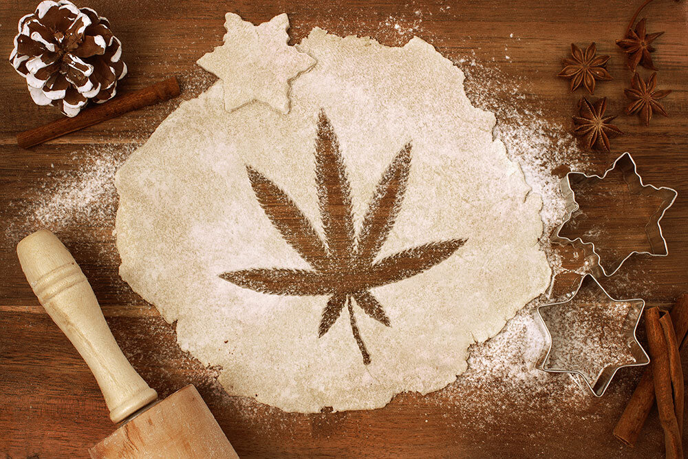 Wooden table with rolling pin and cookie dough with marijuana leaf cut out