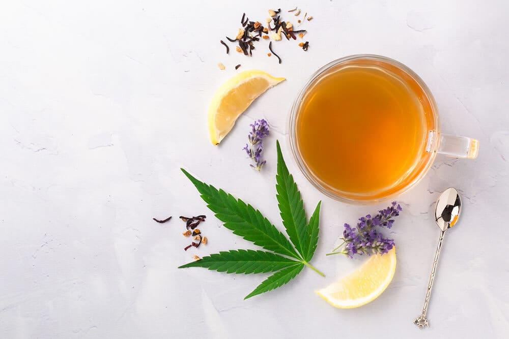 Marijuana leaf, lemon, lavender and cup of tea on marble slab