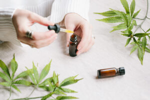 Womans hands holding tincture with marijuana leafs around
