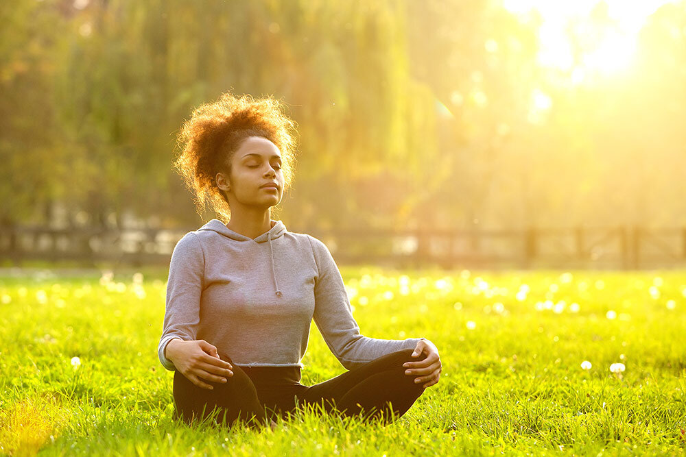 Young woman meditating in grass in outside open area