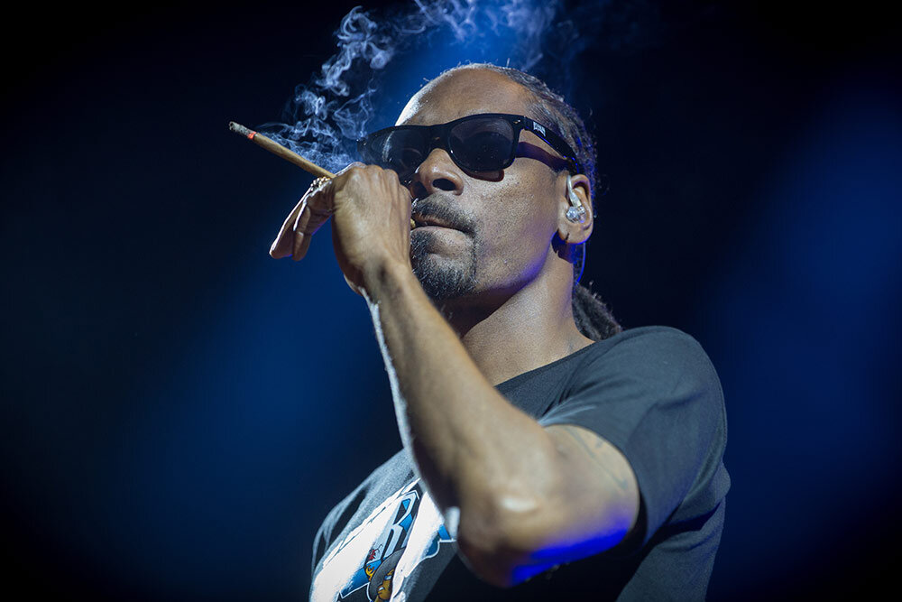 Snoop Dogg smoking joint on stage at concert with sunglasses on