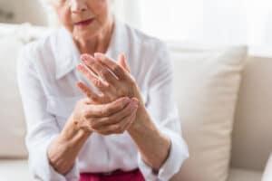 Senior woman with arthritis pain holding hand