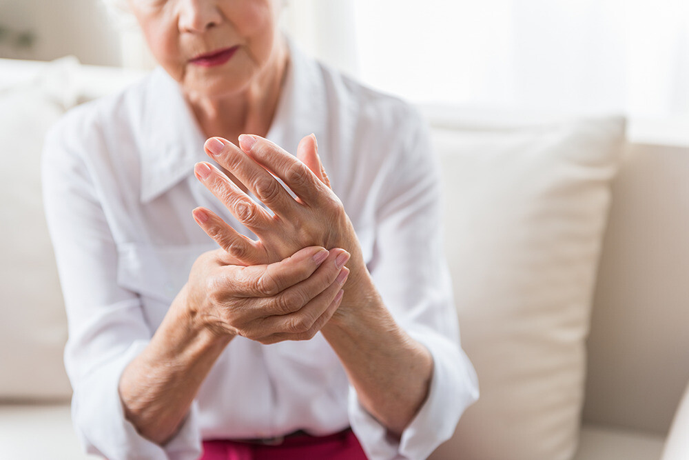 Senior woman with arthritis pain holding hand