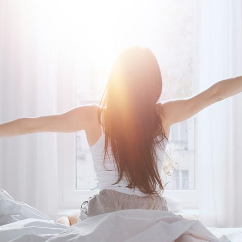 Woman stretching arms waking up from a good nights sleep