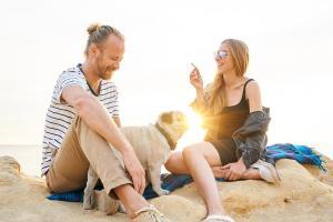 Couple sitting at the beach with their dog smoking weed and having fun