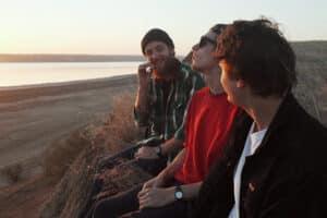 Group of friends sitting at the beach smoking marijuana