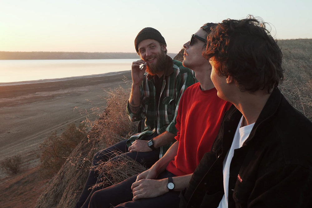 Group of friends sitting at the beach smoking marijuana