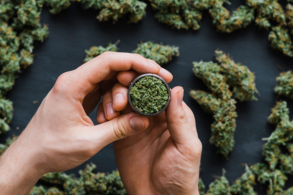 Close up of hand holding jar with cannabis and flower in the background laid out on table