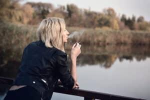 Woman standing on deck near water smoking marijuana