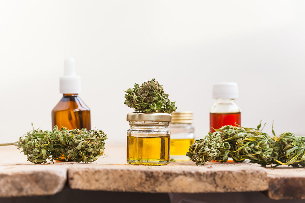 Cannabis flowers and cannabis extracts in jars and tinctures on wooden table