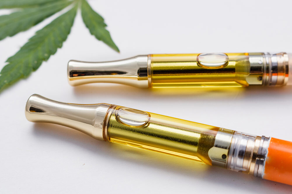 Cannabis plant leaf next to vape pens with cannabis extract