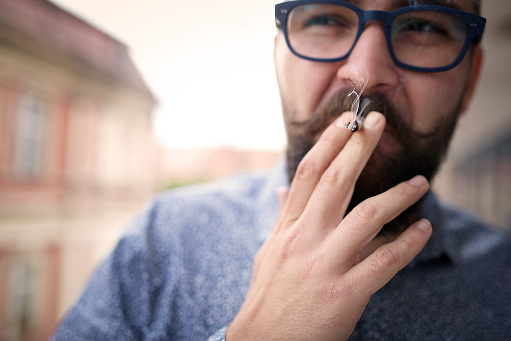 Man walking outside in glasses smoking cannabis blunt