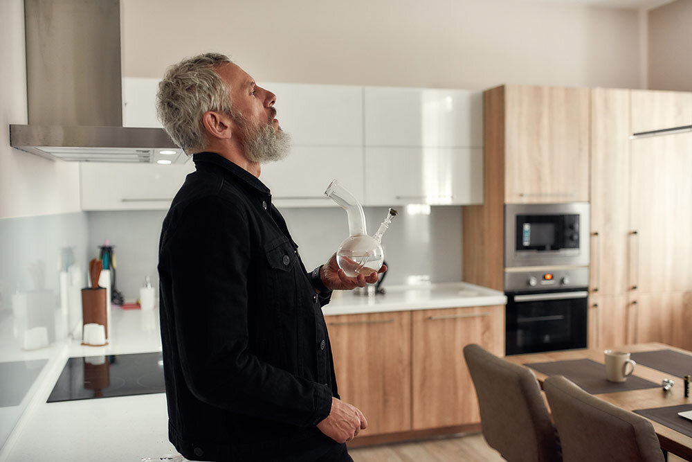 Older man standing in kitchen smoking cannabis flower with bong