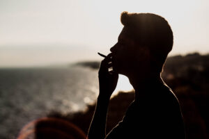Silhouette of man smoking marijuana at the beach with water and sunset in the background