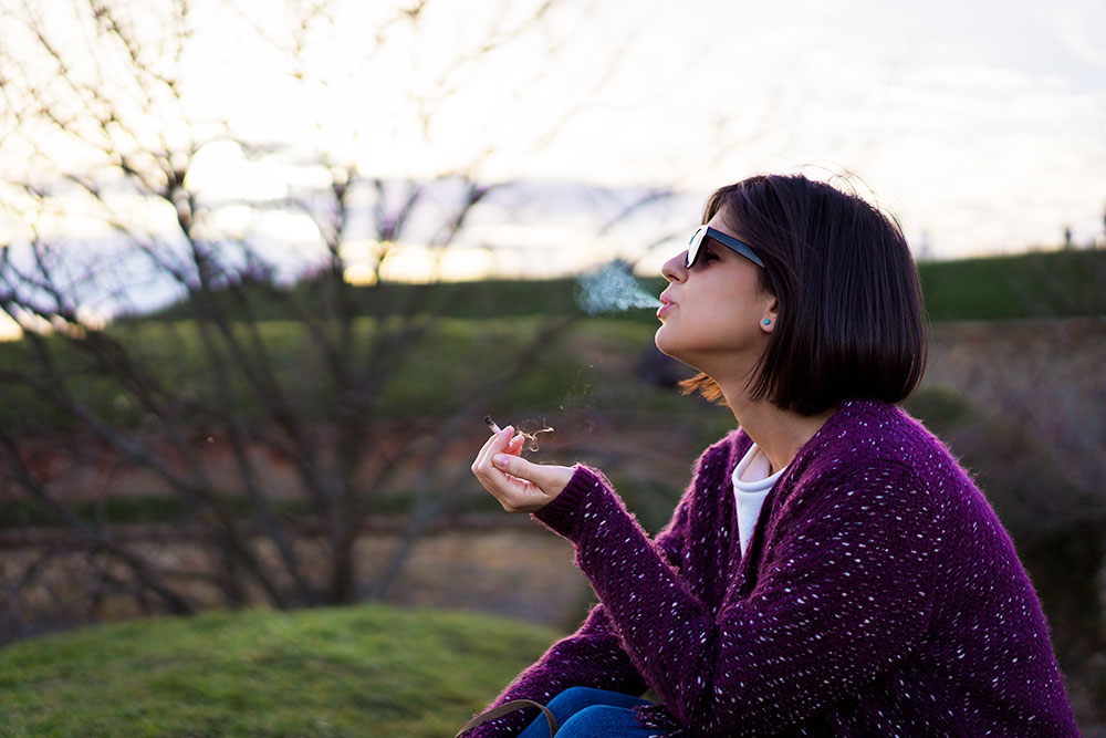 Woman relaxing and smoking weed outside
