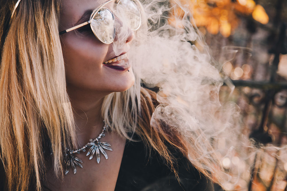 Woman outside smiling in cannabis smoke